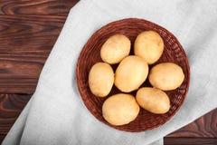 Patatas crudas, crudas y frescas en un fondo de madera Cosecha del verano de los tubérculos de la nueva patata Patatas nutritivas Imagenes de archivo