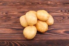 Patatas crudas, frescas y crudas en un fondo de madera del marrón oscuro Producto-vehículos frescos de vegetables Comida natural  Fotografía de archivo libre de regalías