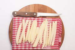 Patatas crudas para las patatas fritas y un cuchillo de cocina de madera Fotografía de archivo