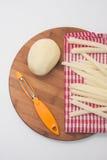 Patatas crudas para las patatas fritas y una herramienta para pelar Imagenes de archivo