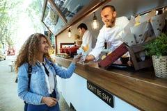 Patatas de compra hermosas de la barbacoa de la mujer joven en un camión de la comida imagenes de archivo