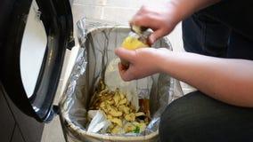 Patatas de la cáscara de las manos del hombre pelado de caída en el cubo de la basura metrajes