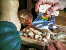 Patatas del corte con el cuchillo del estilo de Ulu Imágenes de archivo libres de regalías