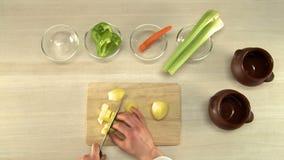 Patatas del corte de la cocina en la opinión superior del tablero de madera almacen de metraje de vídeo
