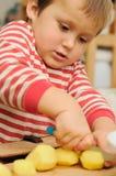 Patatas del corte del pequeño niño Fotos de archivo libres de regalías