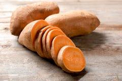 Patatas dulces cortadas en la tabla Fotografía de archivo libre de regalías