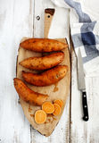 Patatas dulces crudas en tablero de cocinar de madera Fotos de archivo