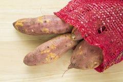 Patatas dulces en un cortador de madera Fotos de archivo libres de regalías