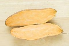Patatas dulces en un cortador de madera Fotografía de archivo