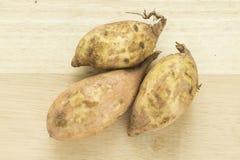 Patatas dulces en un cortador de madera Imágenes de archivo libres de regalías