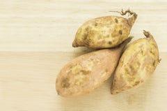 Patatas dulces en un cortador de madera Foto de archivo
