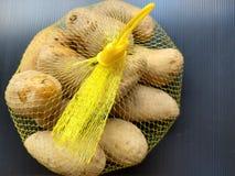 Patatas en bolso de la malla foto de archivo