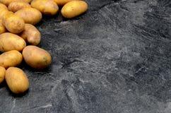 Patatas en fondo negro fotos de archivo