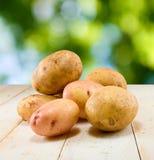 Patatas en la tabla en fondo verde Imagen de archivo