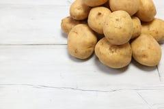 Patatas en un fondo de madera Imágenes de archivo libres de regalías
