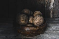 Patatas en una taza en fondo de madera Imagen de archivo libre de regalías