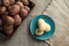 Patatas frescas en una caja de madera oscura en un fondo de la lona de lino Cuatro patatas peladas en una placa imagen de archivo