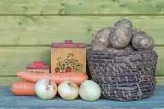 Patatas frescas en una cesta vieja, zanahorias, cebollas y cajas viejas Imagen de archivo libre de regalías