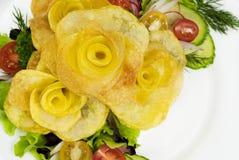 Patatas fritas bajo la forma de rosa en una placa con una ensalada Foto de archivo libre de regalías