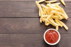 Patatas fritas con la salsa de tomate en fondo de madera Foto de archivo