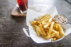 Patatas fritas con la salsa de tomate en la tabla Foto de archivo libre de regalías