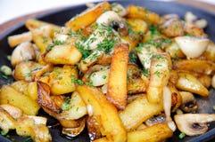 Patatas fritas con las setas en una sartén Imágenes de archivo libres de regalías