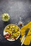 Patatas fritas con los tomates de las setas, de la cebolla y de cereza en la placa blanca en el fondo negro fotografía de archivo libre de regalías