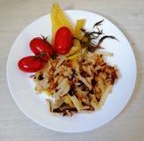 patatas fritas con los tomates y la pimienta imagenes de archivo