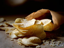 Patatas fritas curruscantes en bolsas de papel en un fondo oscuro Foto de archivo libre de regalías