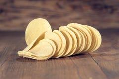 Patatas fritas curruscantes en fondo de madera Imágenes de archivo libres de regalías