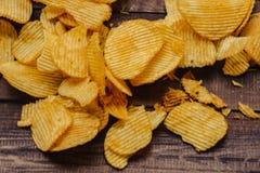 Patatas fritas curruscantes en fondo de madera los microprocesadores comenzaron fotos de archivo