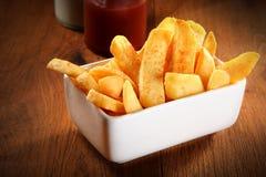 Patatas fritas curruscantes en la placa en la tabla de madera Fotos de archivo libres de regalías