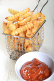 Patatas fritas curruscantes en una cesta de la sartén del alambre con la salsa de tomate Imagen de archivo