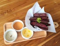 Patatas fritas dulces púrpuras fritas con tres salsas de la inmersión Imágenes de archivo libres de regalías