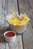 Patatas fritas en cesta del metal con la salsa de tomate de tomate Foto de archivo
