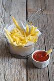 Patatas fritas en cesta del metal con la salsa de tomate de tomate Imagenes de archivo