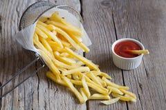 Patatas fritas en cesta del metal con la salsa de tomate de tomate Fotografía de archivo