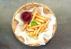 Patatas fritas en cesta en la tabla gris Foto de archivo libre de regalías