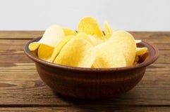 Patatas fritas en placa en la tabla de madera aislada en fondo gris imagen de archivo