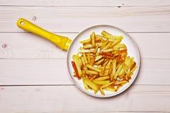 Patatas fritas en una cacerola blanca Foto de archivo libre de regalías