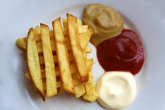 Patatas fritas en una placa con tres clases de salsa fotografía de archivo libre de regalías