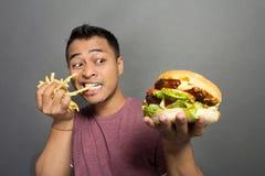Patatas fritas felices de la mordedura del hombre joven y sostener una hamburguesa Fotos de archivo libres de regalías
