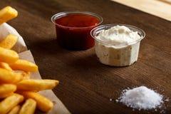 Patatas fritas fritas frescas con la salsa de tomate en fondo de madera Fotos de archivo