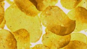 Patatas fritas picantes que hacen girar en el fondo blanco, comida con los reforzadores del sabor metrajes