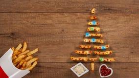 Patatas fritas que forman un árbol de navidad adornado con las luces coloridas almacen de metraje de vídeo