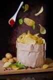 Patatas fritas que vuelan sobre un cuenco Foto de archivo libre de regalías