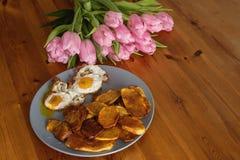 Patatas fritas, ramo de tulipanes rosados y huevos fritos en un fondo de madera Imagen de archivo