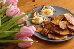Patatas fritas, ramo de tulipanes rosados y huevos fritos en un fondo de madera Fotografía de archivo