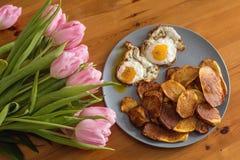 Patatas fritas, ramo de tulipanes rosados y huevos fritos en un fondo de madera Fotografía de archivo libre de regalías