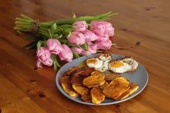 Patatas fritas, ramo de tulipanes rosados y huevos fritos en un fondo de madera Foto de archivo